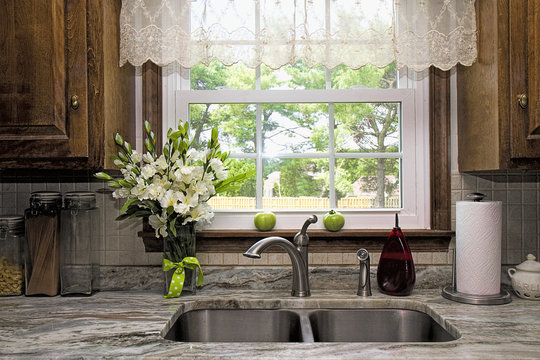 Kitchen view of window and backyard view.  Sheer Valance overhead of double stainless steel sink and granite countertop.  Window seal has two green tomatoes waiting to ripe on it.