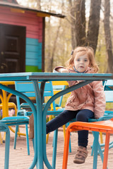 A child girl is sitting at a table outdoors against a background of a spring park