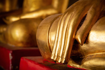 Close focus on fingers and hand of golden Buddha image as meditation posture represents highly concentration.