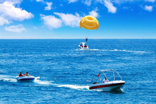 Happy people having fun on inflatable behind speed boat