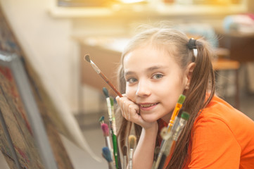 Happy little girl is drawing a picture on easel