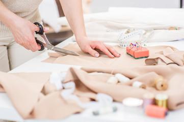 Workplace of seamstress. Close up dressmaker cuts dress detail with scissors