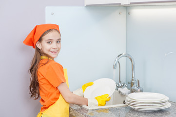 Happy little girl in an apron washes the dishes at the sink