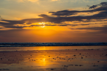 Sunset on the Kuta beach with reflection in the water on the island of Bali
