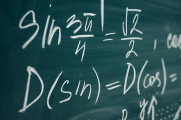 Trigonometric equation written on the chalkboard. School curriculum.