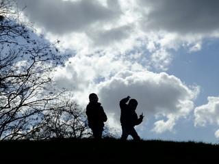2 silhouettes en contre-jour sur une colline