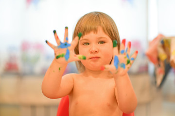 Little cute baby girl paint color by hands and fingers