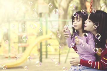 Mother and daughter having fun with soap bubbles at playground.