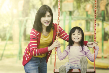 Mother and daughter play together at playground.