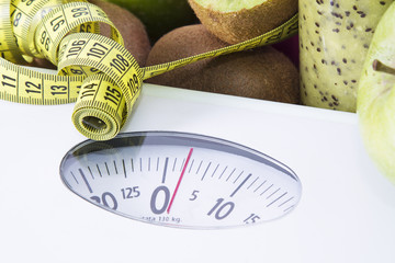 scales with measuring tape and green fruits, concept of healthy diet