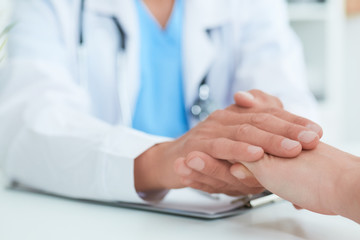 Hand of male doctor reassuring his female patient close-up. Medical ethics and trust concept.