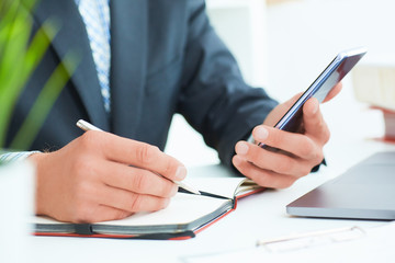Businessman in black suit using mobile smart phone and working on laptop computer close up. Just hands handss over the table.