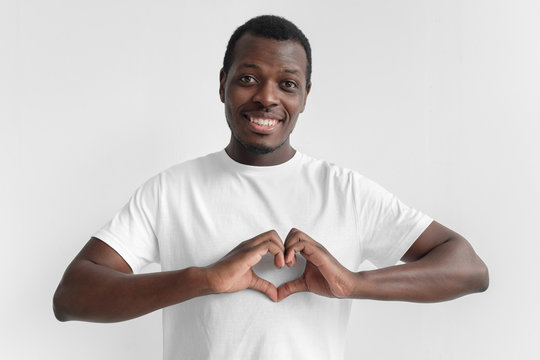 Portrait of young smiling dark skin african american man in white t shirt showing heart sign isolated on gray background