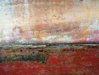 Abstract background of old decaying wooden boat panels painted in red and white