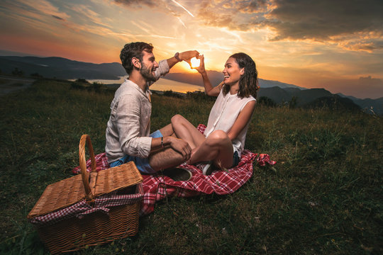 Portrait of young couple having good times on a picnic date, behind them is a beautiful sunset over Boka Bay