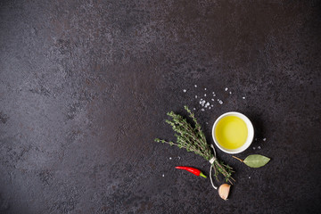 Olive oil and bouquet of thyme on a black stone background