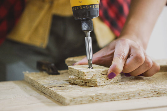 Crop view of female hand driving self-tapping screw into chipboard placed on wooden workbench on blurred background