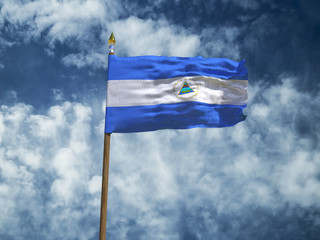 Nicaragua flag Silk waving flag of Nicaragua made transparent fabric with wooden flagpole gold spear on background sunny blue sky white smoke clouds real retro photo Countries of world 3d illustration