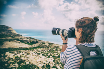 Young woman professional photographer and traveler takes pictures of the landscape on the sea and hills, beautiful nature, profession, vacation and travel concept
