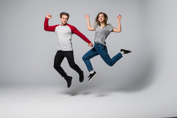 Full length portrait of a cheerful young couple jumping and running over white wall