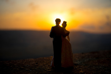 silhouette of wedding Couple statue holding hand together during sunset with evening sky background. Wedding concept.