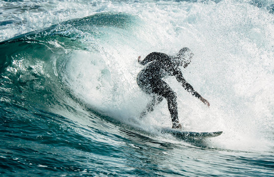 Silhouette of a surfer surfing a wave in the north of Spain