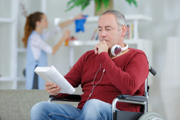 frustrated man in wheelchair reading book