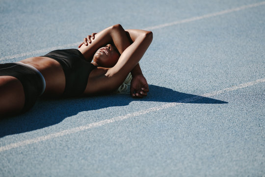 Female athlete relaxing on running track after workout