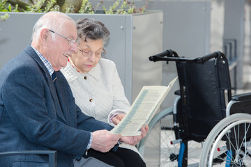 nice elderly couple sitting outdoors with book