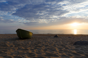Old fisherman boat at sunset time. Sunset at the Baltic Sea Beach.
