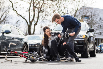 Reliable young man helping an injured woman while waiting for the ambulance after bicycle accident on city street