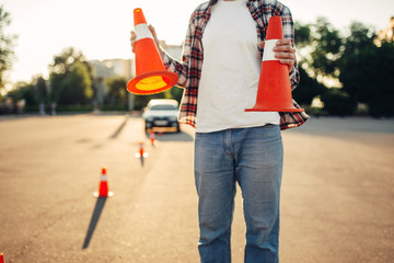Fototapete - Male vehicle instructor holds cones in hands