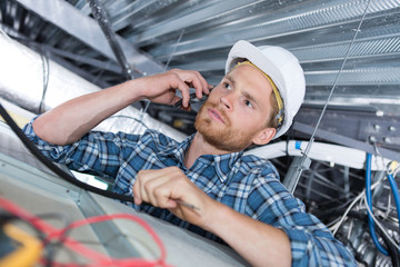 young handsome electrician on the phone