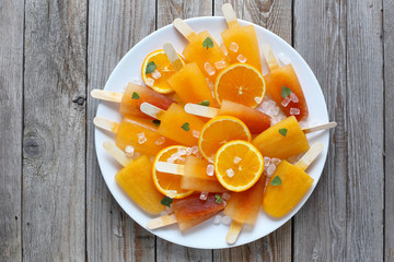 Orange ice pops on old wooden table