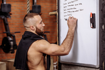 muscular fit guy is writing his training program on the board. sport and lifestyle concept