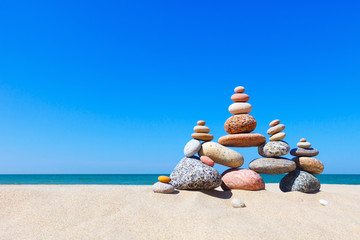 Poster de jardin Zen pierres a sable Rock zen pyramid of colorful pebbles on a sandy beach on the background of the sea. Concept of balance, harmony and meditation.