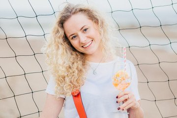 Horizontal shot of cheerful glad blonde female dressed in casual clothes, holds fresh orange cocktail, smiles positively, poses against tennis net background at beach. Woman with summer beverage