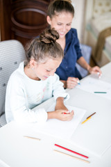 Happy family. Mother and daughter together paint and draw. Adult woman helps the child girl