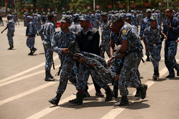 Federal policeman carry their injured colleague during clashes at a protest following the burial ceremony of Simegnew Bekele, Ethiopia's Grand Renaissance Dam Project Manager, who was found dead in his vehicle on Thursday, in Addis Ababa