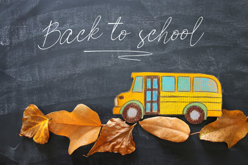 Back to school concept. Top view image school bus over autumn dry leaves classroom blackboard background.