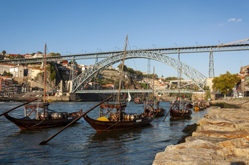 View of the Douro River with rabelo boats, the iconic Dom Luis Bridge and the Ribeira neighbourhood in Porto, Portugal; Concept for travel in Portugal and visit Porto