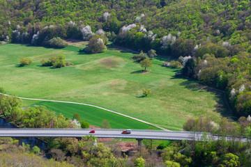 Straße mit Autos durch grüne bewaldete Landschaft