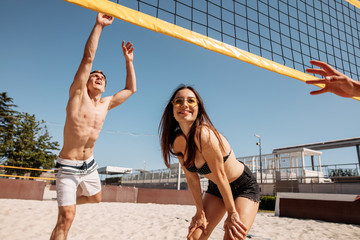 Young positive caucasian people in good physical form playing volleyball on beach. Athletic men and women enjoying active leisuretime outdoors on vacation