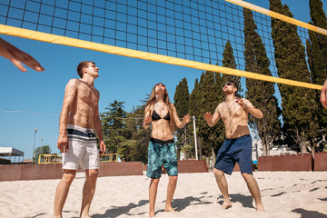 group of fit cheerful guys and girls, dressed in beach outfit, playing volleyball in sunny day during their summer holidays.