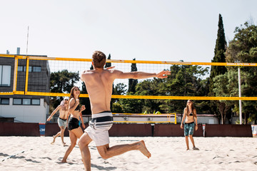 People on vacation playing beach volleyball sport. Young sportive and positive men and women having fun recreational volley ball game in summer living healthy active sport lifestyle.