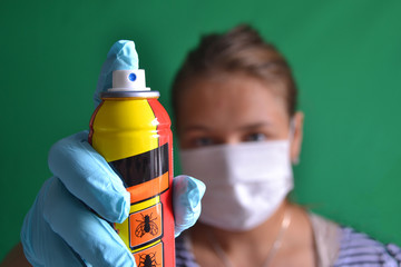 Aerosol for insect control in the hands of a woman wearing a mask.
