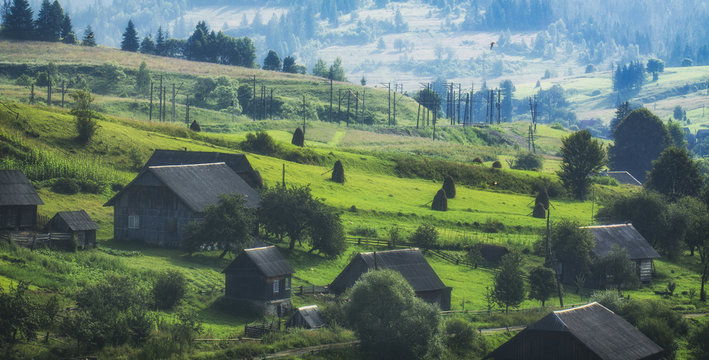A small village in the mountains, on the slopes covered with green grass