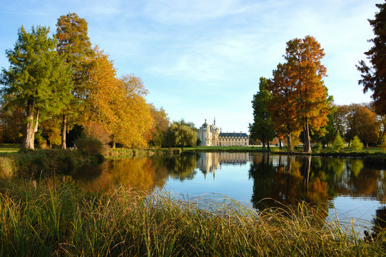 View of Chantilly castle reflected in pool surrounded by park trees. Autumn. France.