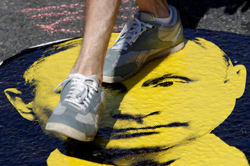 A man steps on the portrait of Russia's President Vladimir Putin during a protest over government's decision to increase the retirement age in Moscow