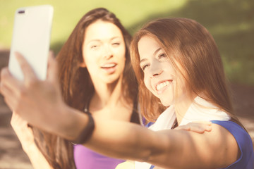 Millennials lifestyle concept - two sports girls take a selfie and smile while training outdoors on a sunny day ( vintage effect)